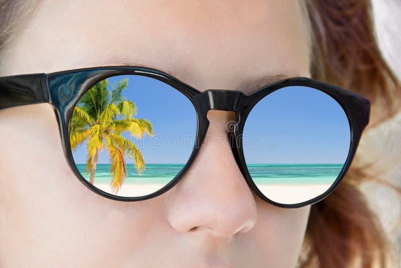 Солнечные очки девушки, отражение пляжа, концепция лета стоковые изображения