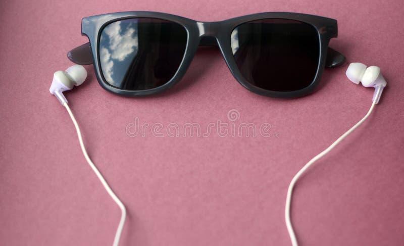 Солнечные очки и наушники на пастельной розовой предпосылке стоковые фото