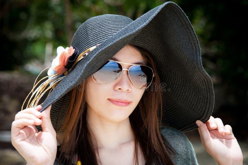 Солнечные очки красивой молодой азиатской женщины крупного плана нося и шляпа пляжа ослабляя на пляже стоковая фотография rf