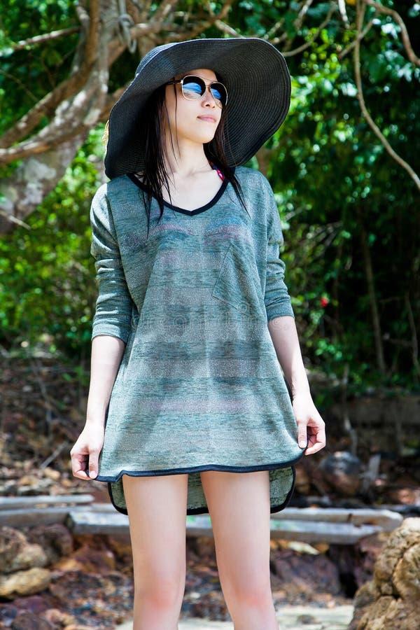 Солнечные очки красивой молодой азиатской женщины нося и шляпа пляжа ослабляя на пляже стоковые фото