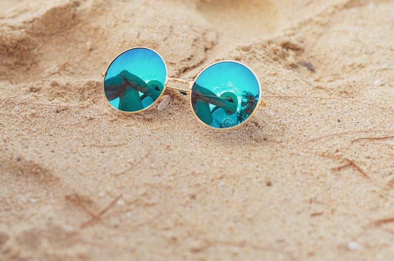 Солнечные очки положили дальше пляж песка Отражение женщины сидит на пляже песка в солнечных очках Соломенная шляпа женской одежд стоковые фотографии rf