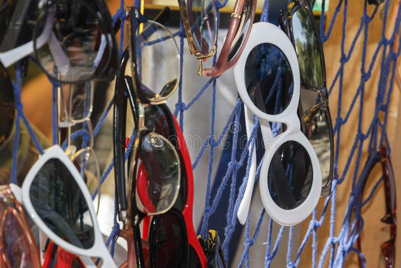 Солнечные очки разных видов повешены на покрашенных потоках для продажи на подносе улицы изображение энергии принципиальной схемы стоковая фотография