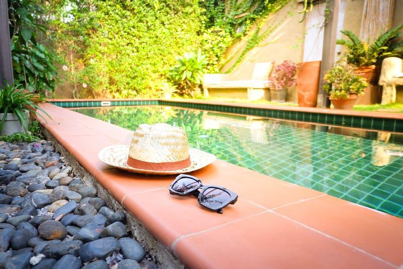Солнечные очки с винтажным fasion соломенной шляпы на бассейне, предпосылке нерезкости для винтажного курортного отеля стоковое фото