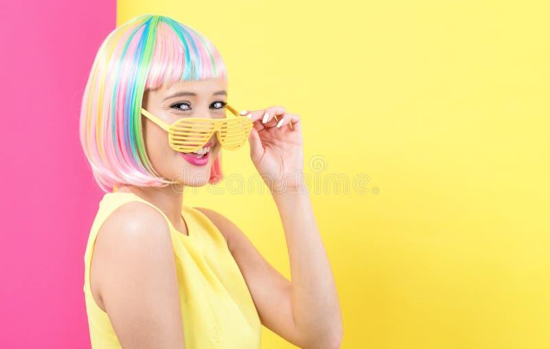 Солнечные очки теней шторки женщины нося в красочном парике стоковая фотография