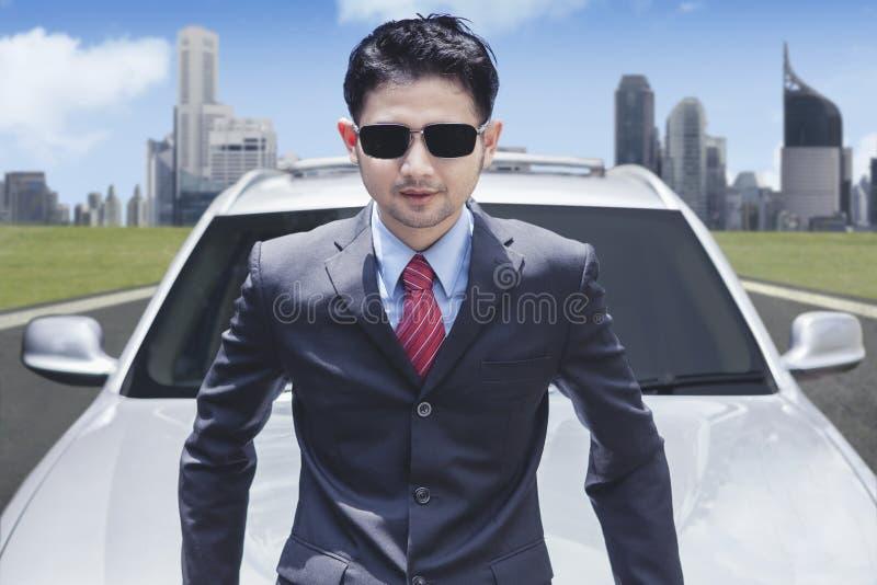 Солнечные очки успешного бизнесмена нося перед роскошным автомобилем с предпосылкой городского пейзажа стоковое фото rf
