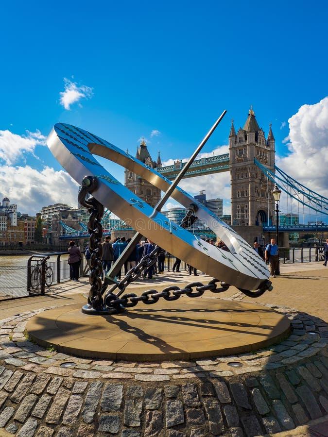 Солнечные часы на доках St Katharine и мост башни над рекой Темза в Лондоне, Великобритании на солнечный день стоковые фото