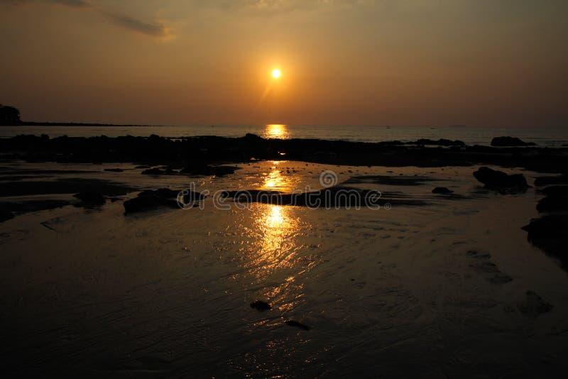 Солнечный луч во время захода солнца бросая длинный желтый луч света над океаном стоковая фотография rf