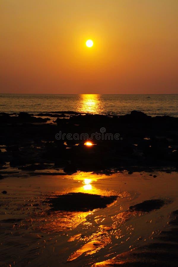 Солнечный луч во время захода солнца бросая длинный желтый луч света над океаном стоковое изображение