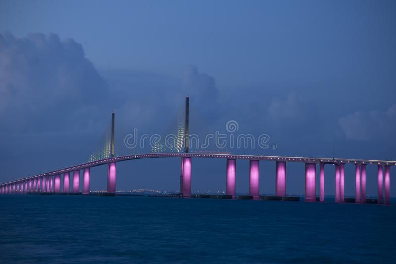 Солнечный мост Скайуэй в Тампа-Бэй Флорида осветил розовыми огнями в память о месяце повышения осведомленности о раке груди стоковое изображение