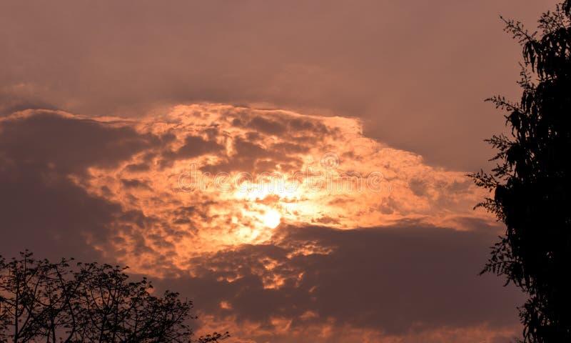 Солнечный свет и небо заволакивают предпосылка в празднике вечера, выглядеть как вулкан в небе, чувстве горячем, теплом и романти стоковое фото rf