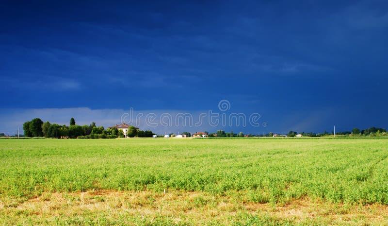 Солнечный свет между штормом на сельской местности долины Po, Италия стоковая фотография rf