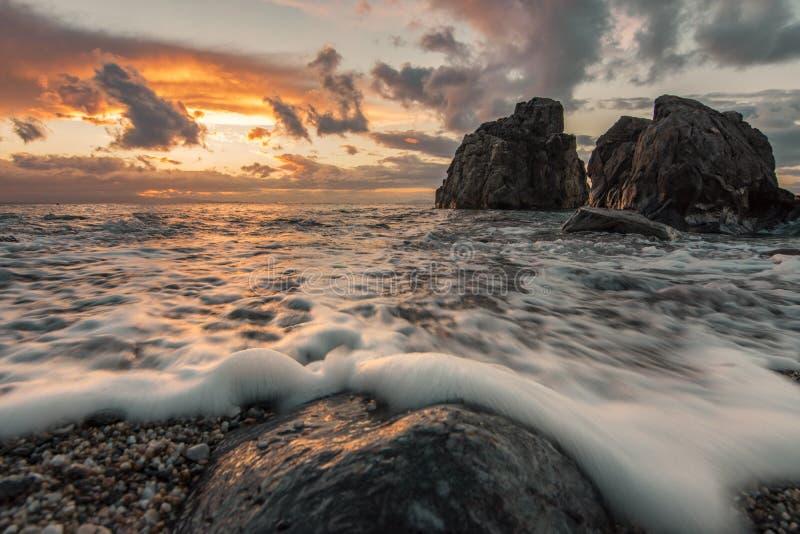 Солнечный свет на волне захода солнца на переднем плане изумляя утесы перспективы в пляже стоковое изображение rf