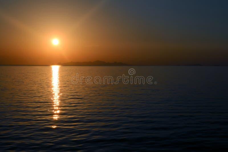 Солнечный свет отражает к морю с фиолетовым заходом солнца неба стоковое фото