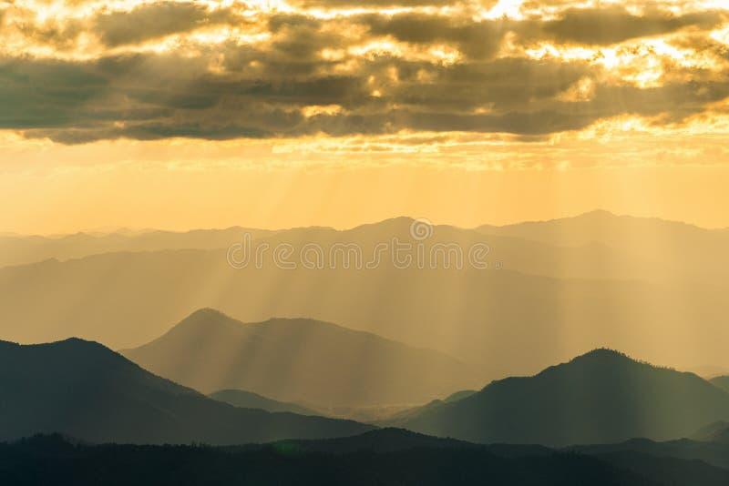 Солнечный свет светя через облака на туманную гору в Таиланде стоковое изображение rf