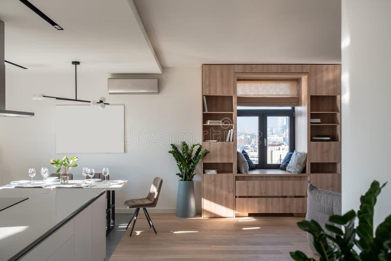 Солнечный современный интерьер с белыми стенами и зоной кухни стоковая фотография