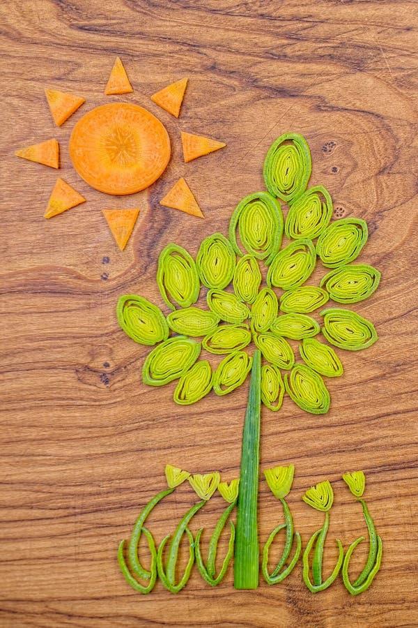 Солнце, дерево и цветки сделанные лук-порея и кусков моркови на деревянной предпосылке разделочной доски стоковая фотография