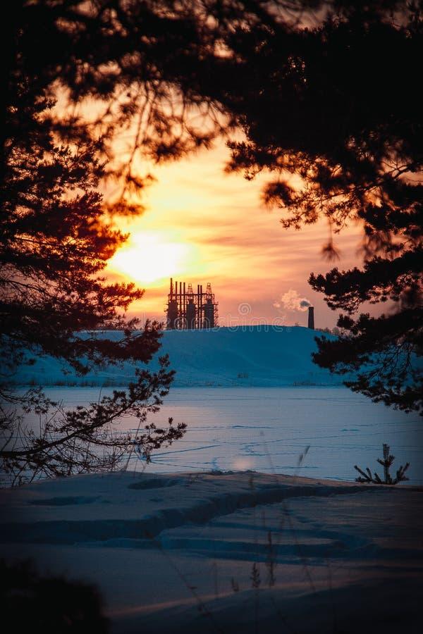 Солнце над заводом на заходе солнца зимнего дня стоковое фото