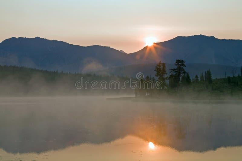 Солнце поднимая над горой и отражением в озере стоковые изображения