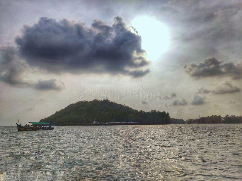 Солнце, причаливая облако и шлюпка под стоковая фотография rf