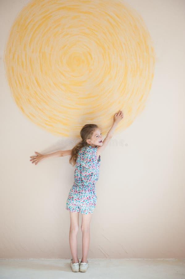 Солнце счастливой маленькой красивой девушки касающее желтое покрашенное на стене в новой квартире дома стоковые изображения rf