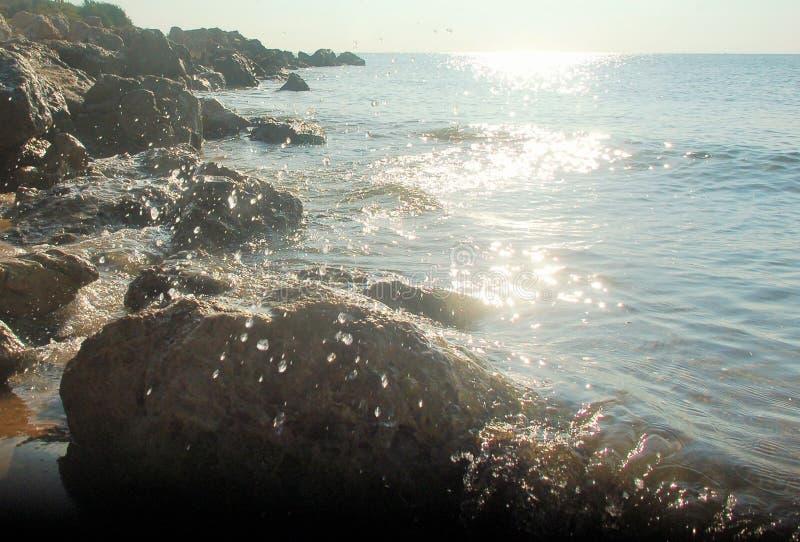 Солнце, трясет, отражает и море стоковые фото