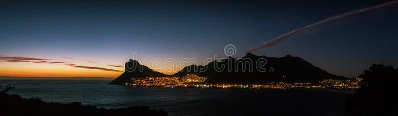 Солнце устанавливает за заливом Hout, при пик часового silhouetted против золотого света стоковое фото