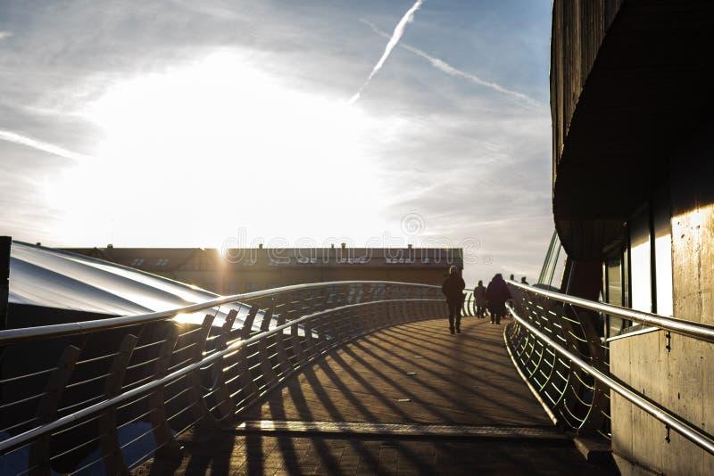 Солнце устанавливая за зданиями в Jelgava, Латвии Взгляд от моста Mitavas стоковое изображение rf