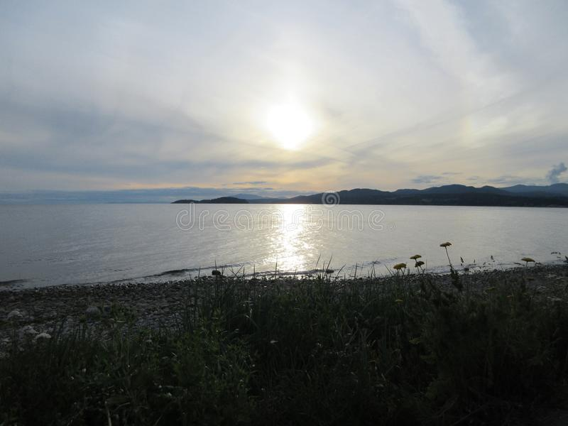 Солнце устанавливая над скалистым пляжем стоковое фото rf