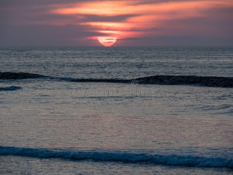 Солнце целуя океан на заходе солнца на Kuta Бали стоковое фото rf