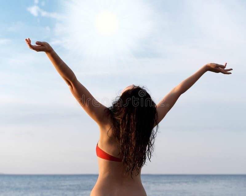 солнце seacoast приветствию девушки стоковое изображение rf
