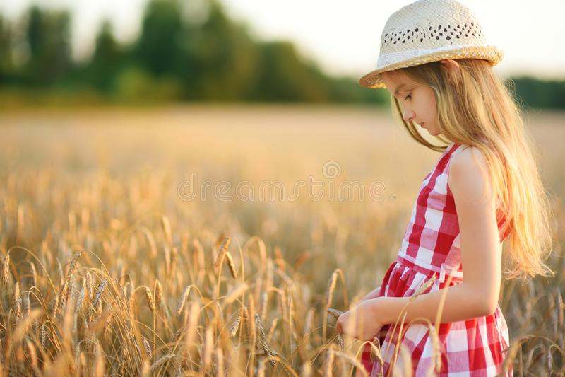 Соломенная шляпа прелестной девушки нося идя счастливо в пшеничное поле на теплом и солнечном вечере лета стоковые изображения