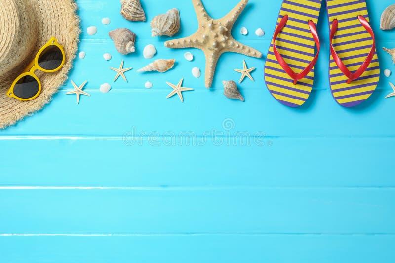 Соломенная шляпа, солнечные очки, темповые сальто сальто и много морских звёзд на предпосылке цвета деревянной, космос для текста стоковое фото rf