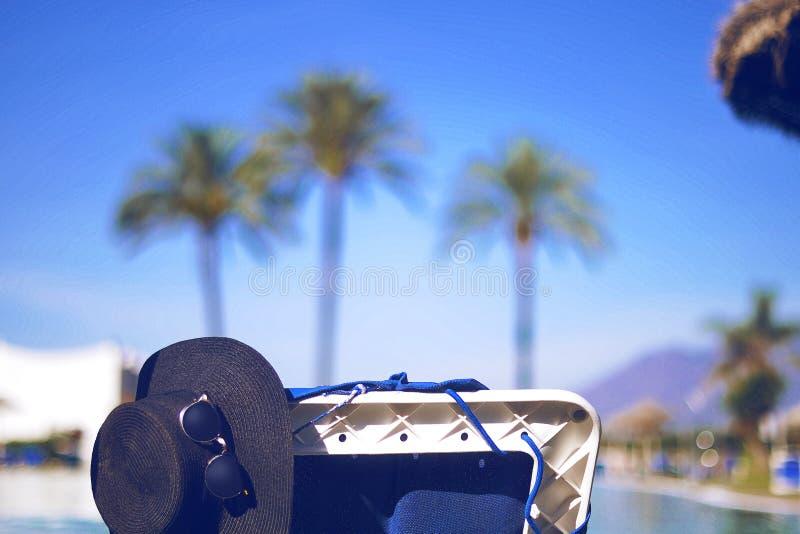 Соломенная шляпа, стекла солнца на lounger, около бассейна На пальмах и горах предпосылки Самые лучшие остатки, загар, солнечный  стоковое изображение