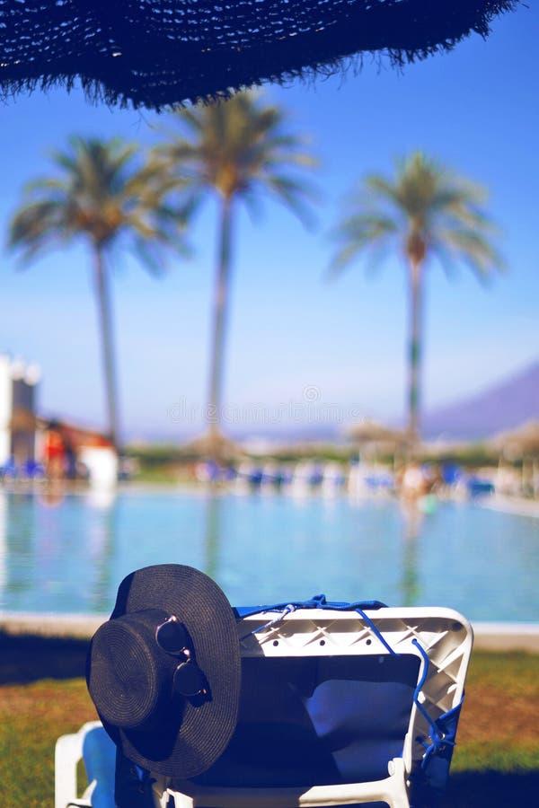 Соломенная шляпа, стекла солнца на lounger, около бассейна На пальмах и горах предпосылки Самые лучшие остатки, загар, солнечный  стоковые фото