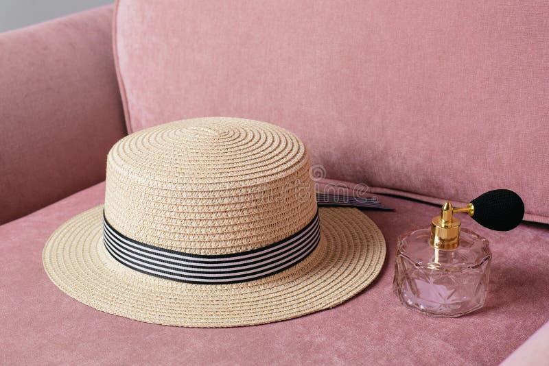 Соломенная шляпа с духами на розовой предпосылке моды стула стоковое фото