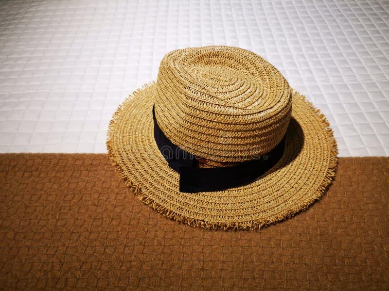 Соломенная шляпа с черной лентой на крышке кровати стоковые фото