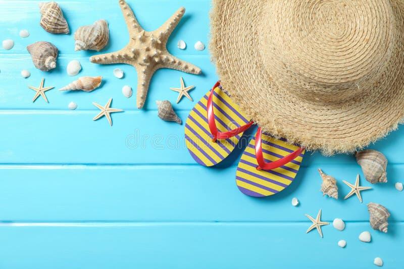 Соломенная шляпа, темповые сальто сальто и много морских звёзд на предпосылке цвета деревянной, космос для текста и взгляд сверху стоковые фотографии rf
