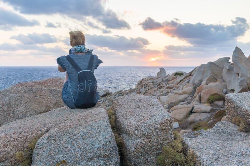 Сольный молодой женский путешественник наблюдает красивый заход солнца на эффектных утесах Testa каподастра, Сардинии, Италии стоковые изображения rf