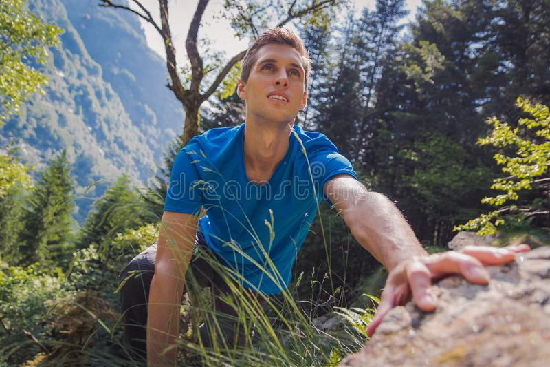 Сольный человек взбираясь утес в лесе стоковые фотографии rf