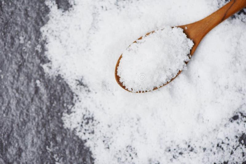 Соль в деревянных ложке и куче белого соли на темном взгляде сверху предпосылки стоковое изображение