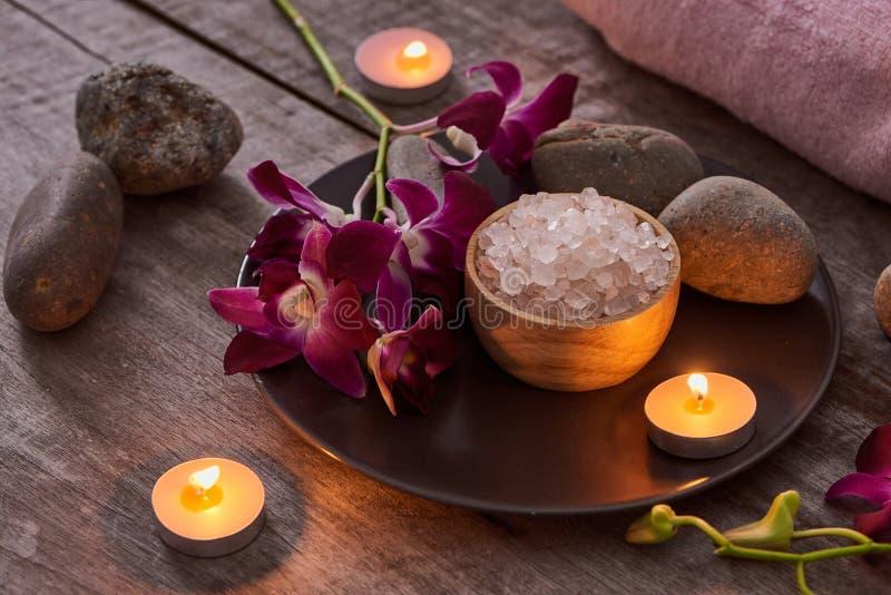 Соль для принятия ванны на бамбуковом шаре и орхидеях цветет на темной древесине стоковое фото