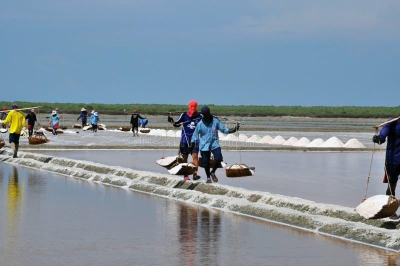Сол-работники в маске носят соль на их плече стоковая фотография