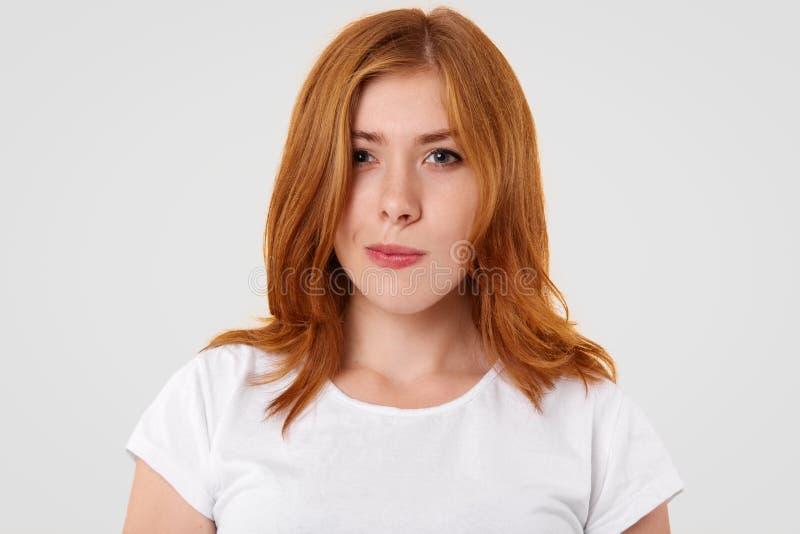 Сомнительные довольно женские губы и взгляды портмон с неуверенностью, имеют рыжеватые волосы, одетые в вскользь футболке, попытк стоковые фото