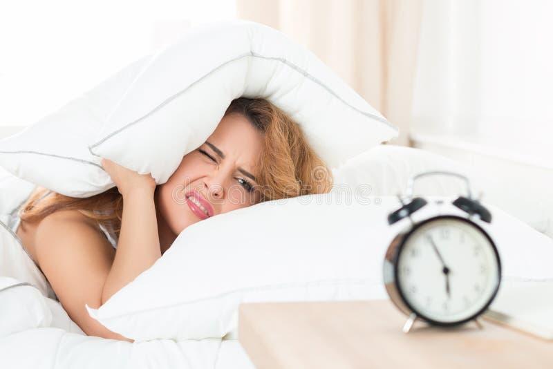 Сонная девушка смотря будильник и пробуя спрятать под стоковая фотография