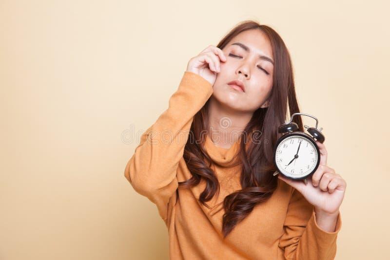 Сонная молодая азиатская женщина с часами в утре стоковое изображение rf