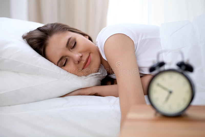 Сонная молодая женщина брюнет протягивая руку к звеня повороту сигнала тревоги охотно готовому оно  Предыдущее бодрствование ввер стоковые изображения