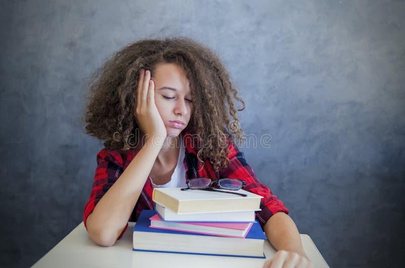 Сонная предназначенная для подростков девушка отдыхая от учить стоковое изображение rf