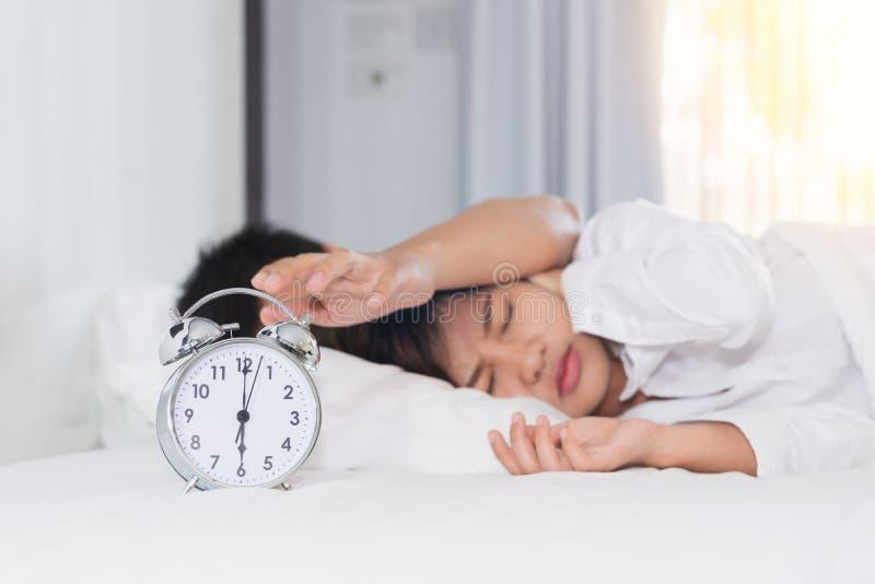 Сонный пробовать человека поворачивает будильник около женщины надоеданной мимо стоковое изображение