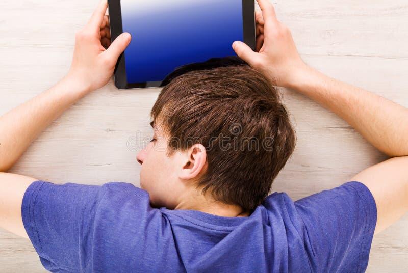 Сон молодого человека с таблеткой стоковое изображение