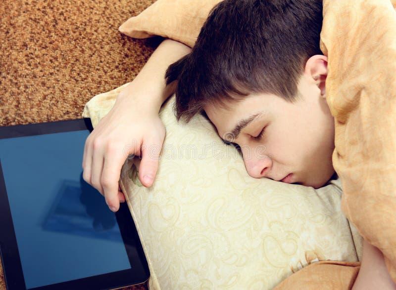 Сон подростка с таблеткой стоковые изображения rf